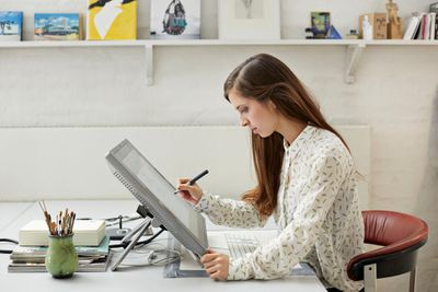 Graphic designer drawing on computer screen