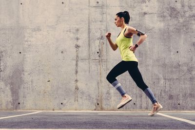Woman running with activity tracker
