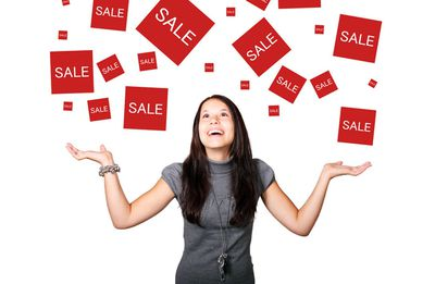 Photo of a woman with sale signs above her head.