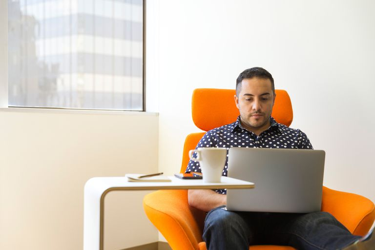 Man using laptop on orange chair