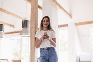 Image of woman laughing while using iPhone
