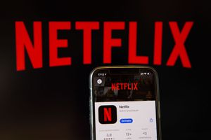 An iPhone showing the Netflix app with a large Netflix logo in the background
