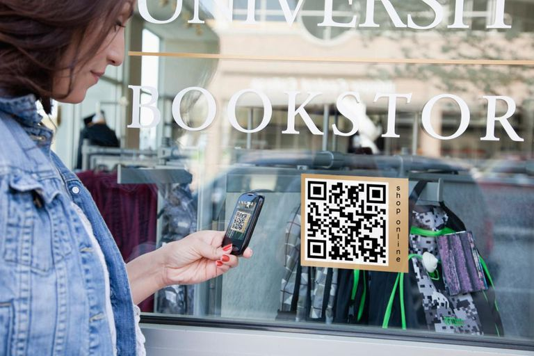 Woman with smartphone reading QR code from window display