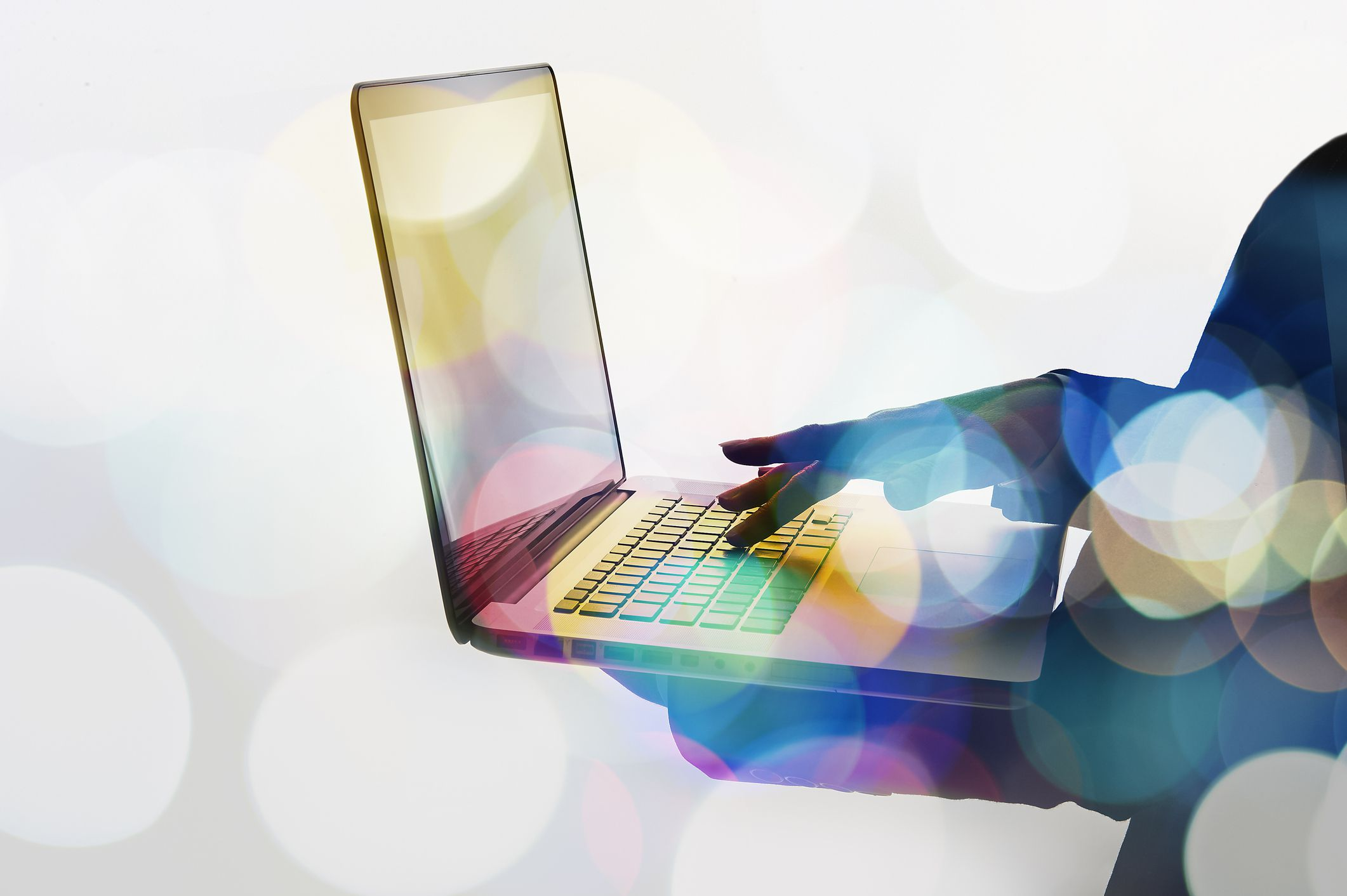 Someone holding a laptop and typing with one hand, image overalyed with bokeh lights.