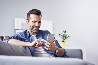 Person holding a cellphone and smiling