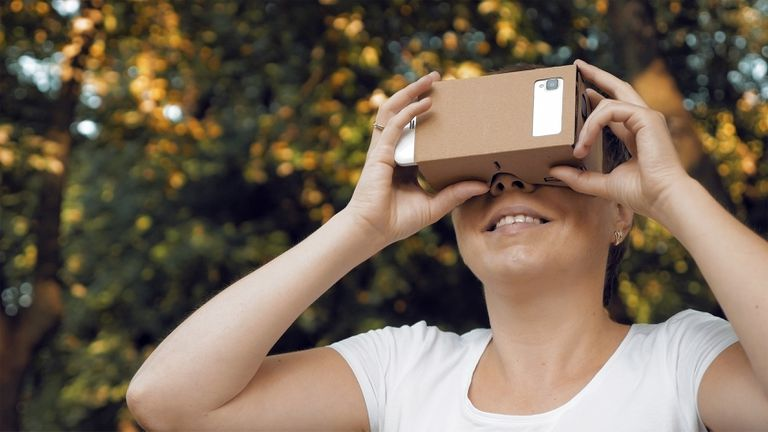 Person using smartphone with Google Cardboard headset