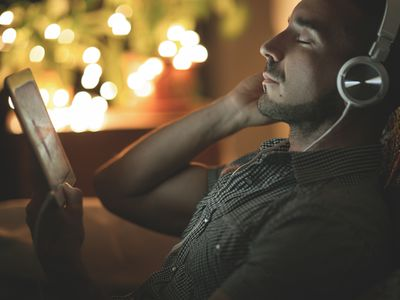 Relaxed, bearded person listening to music at night
