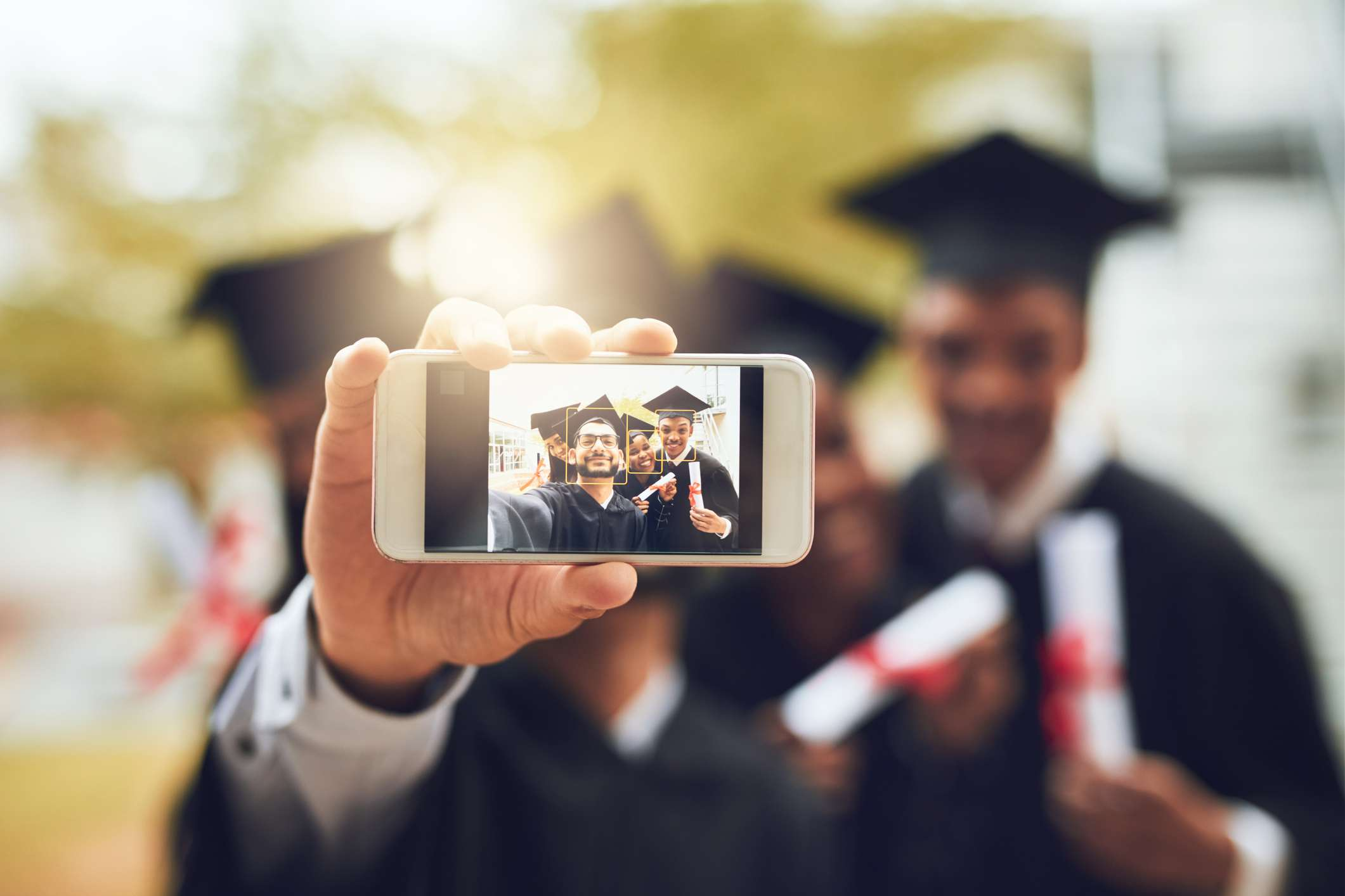 A group of graduates taking a smartphone selfie with facial recognition enabled.