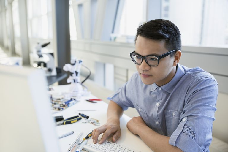 Picture of a man in glasses and a blue shirt using a white computer