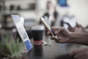 Hand holding smart phone, scanning barcode