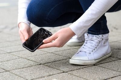 Midsection of woman holding mobile phone with cracked screen