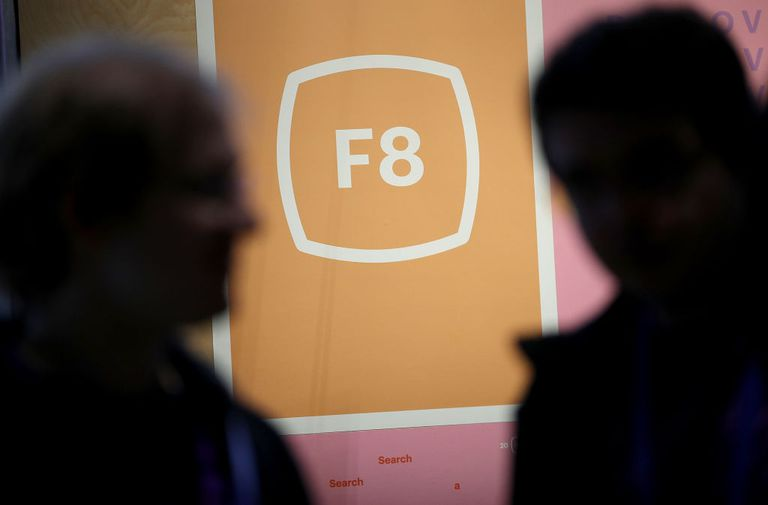 F8 logo on a screen with two silhouettes in foreground
