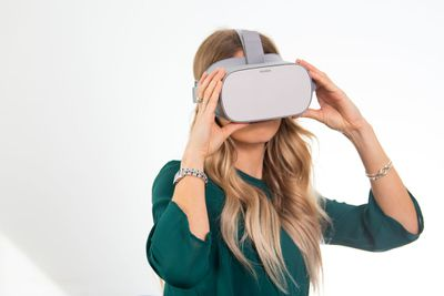 A woman uses a pair of virtual reality goggles.