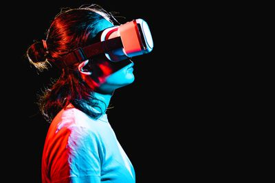 Woman using VR headset while lit up by red and blue lights