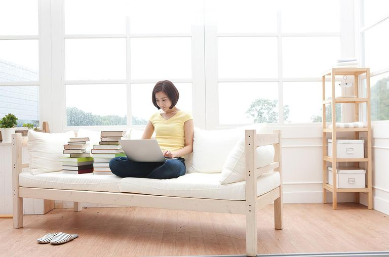 Woman using laptop in clean living room next to stack of books