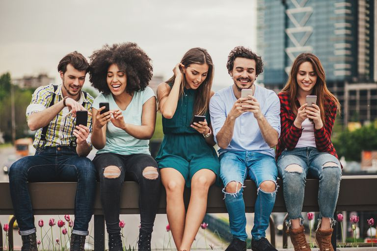 5 friends sit on bench with phones organizing Facebook friends lists