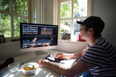 A man editing videos on a Mac computer
