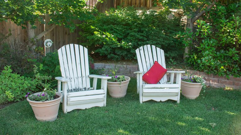 A home garden with some wooden chairs