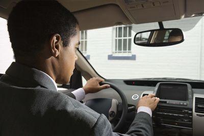 Man in car adjusting radio in a car