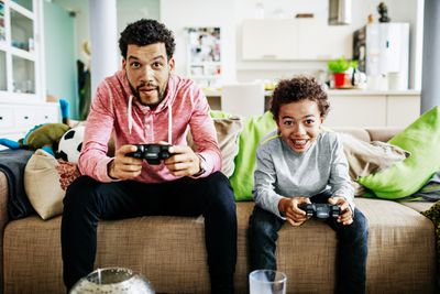 A man and his son sitting on a sofa playing a game while concentrating deeply