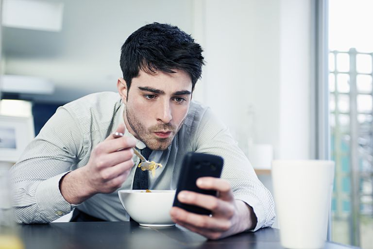 Man staring at his phone as he eats cereal, depicting Facebook addiction