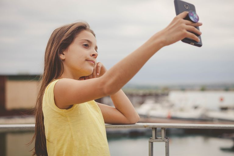A young girl taking a selfie holding a smartphone with a PopSocket.