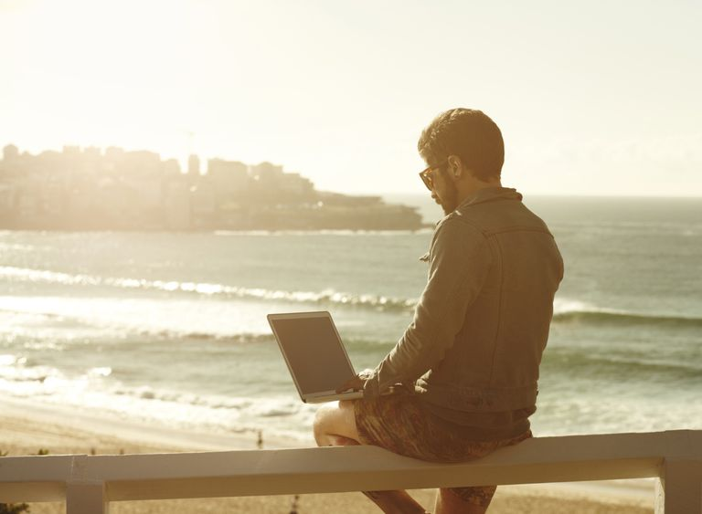 Man on a sunny beach using laptop