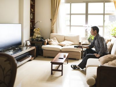 Man using a remote on his couch