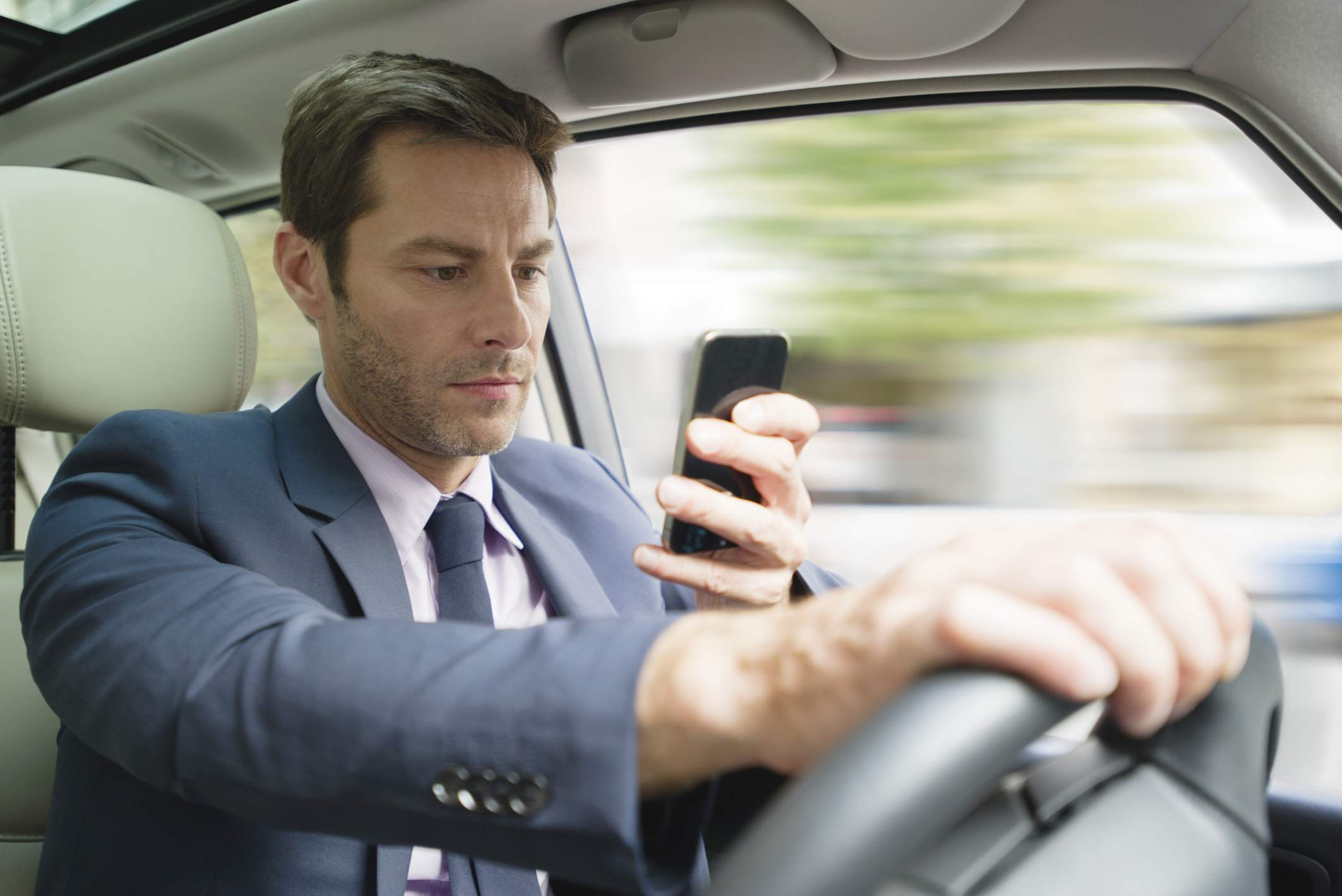 Taxi driver in a suit texting while driving