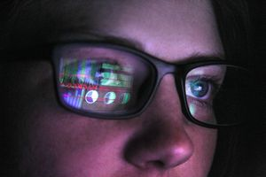 An image of a person viewing computer data, the data reflecting in her glasses.