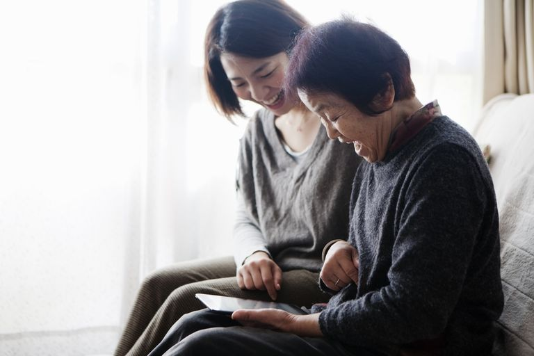Young woman and older woman watching a digital tablet together