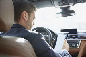 Over the shoulder view of young businessman using digital tablet in car