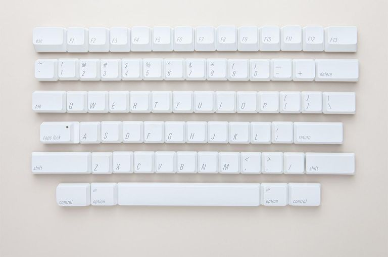 Dismantled white keyboard on pink background.