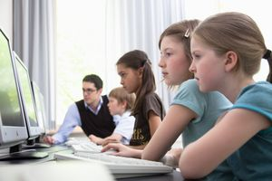 Male teacher helping pupils in computer room, Hamburg, Germany