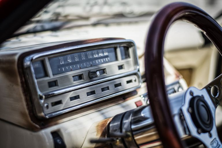 A photo of an old car radio in an antique car.