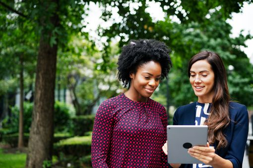 Two women looking at a tablet while standing in a park