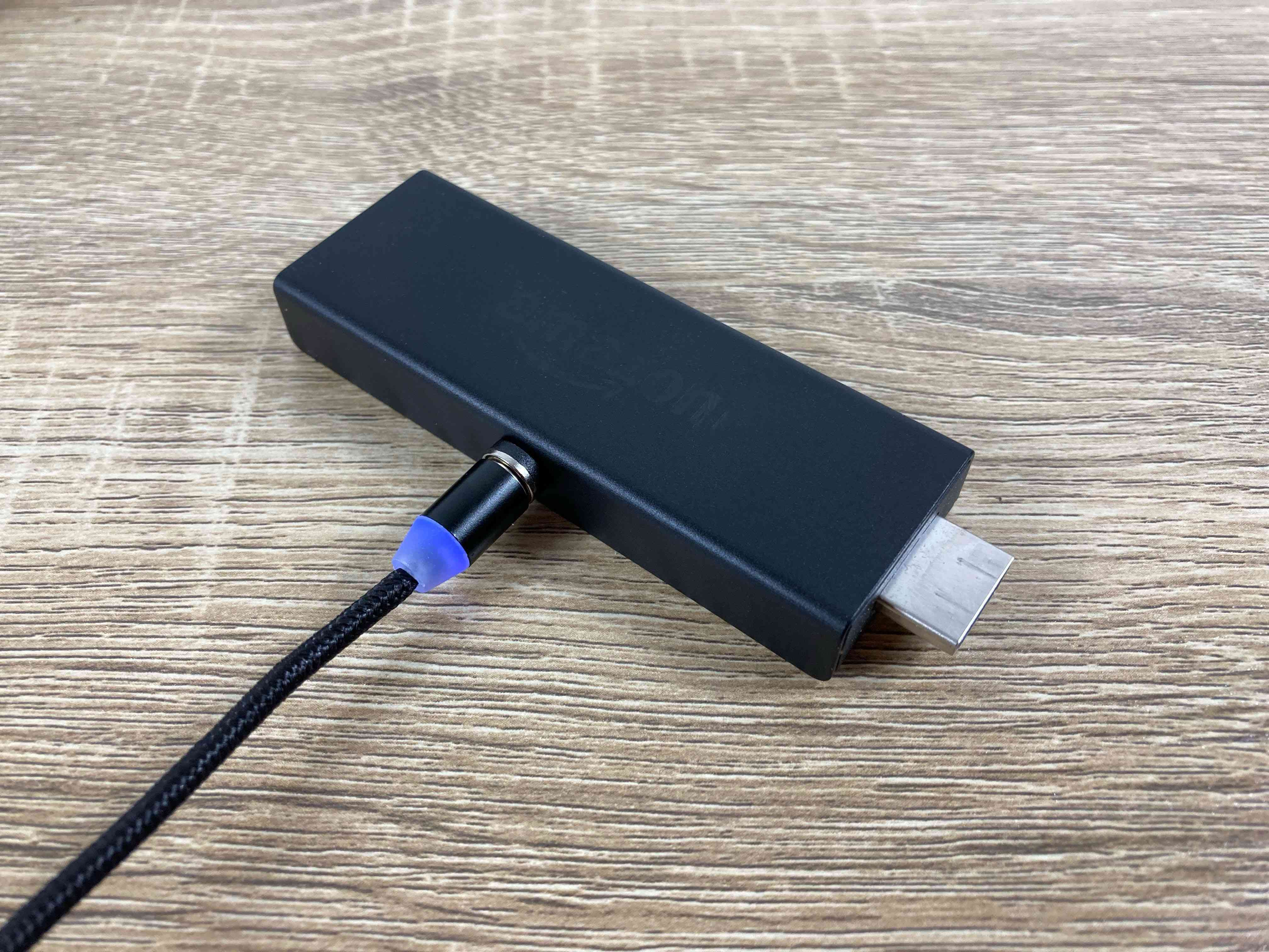 A Fire Stick plugged into a USB power source.