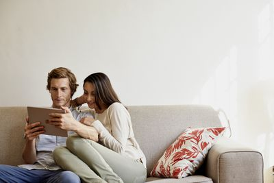 Couple using digital tablet on sofa at home