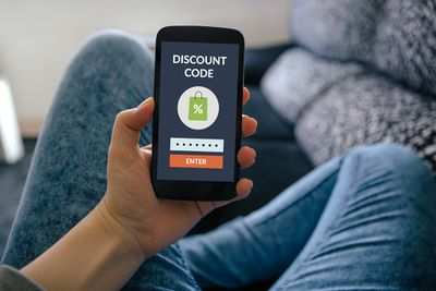 Girl holding smart phone with discount code concept on screen