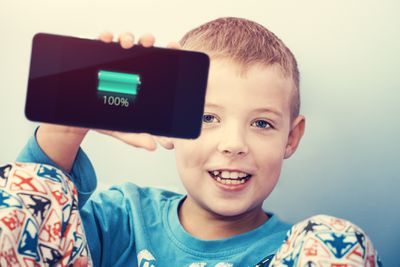 A kid holding up a fully charged smartphone