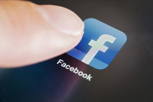 A finger taps the Facebook app icon on a smartphone.