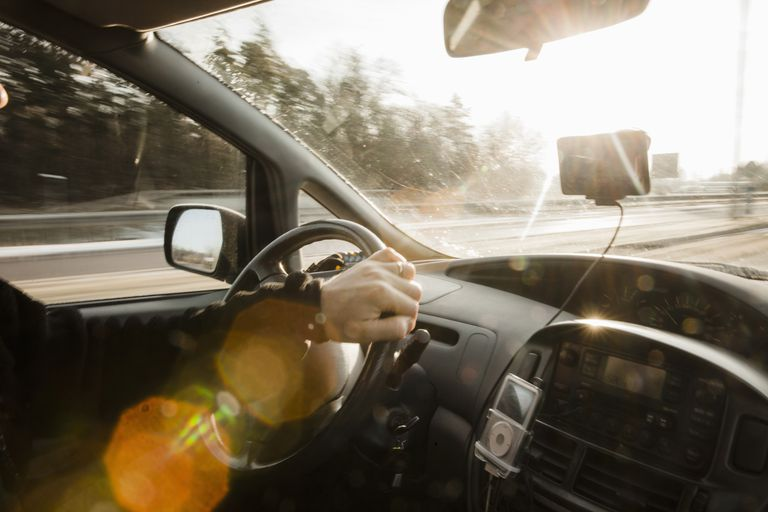 A woman listens to her ipod in her car with an FM transmitter