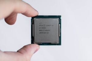 Close up of person holding an Intel Core i9 processor with the tips of their fingers.
