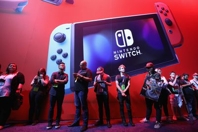 People standing in front of a Nintendo Switch image.
