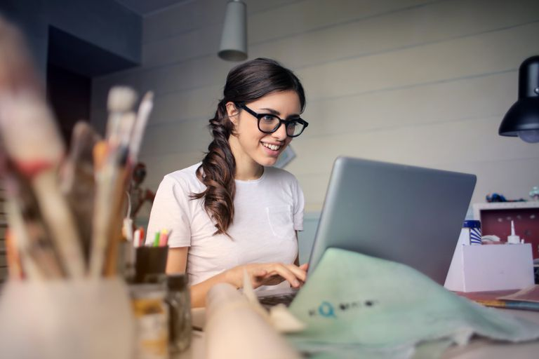 Woman wearing glasses while working on laptop