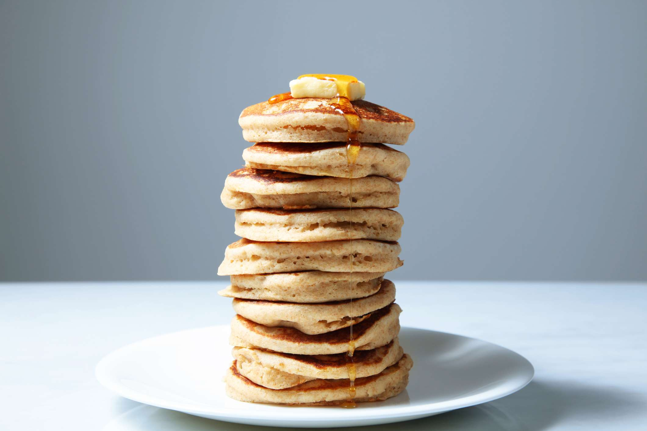 A large stack of fluffy, wheat pancakes, topped with a pad of yellow butter and golden maple syrup