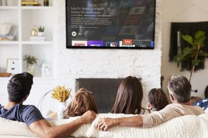 A family sitting on a lounge while downloading fuboTV on their Amazon Fire TV Stick that's connected to their television.