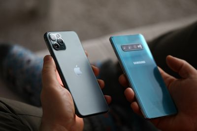 An iPhone and Samsung phone held side by side