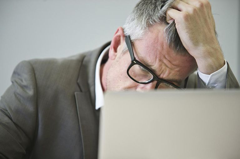 Stressed mature businessman in office