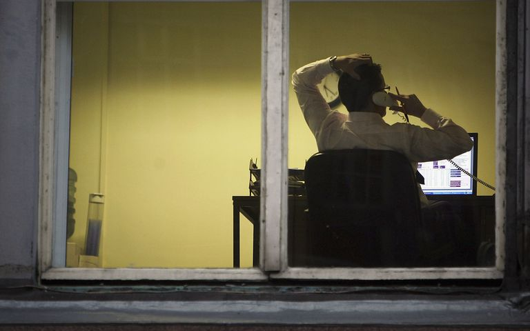 Man on the phone at his desk through a window